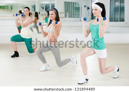 Three girls in fitness club workout with dumbbells - stock photo
