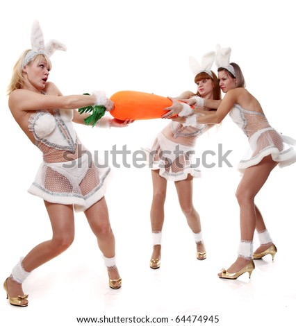 Three girls in suits of a rabbit divide the big carrot