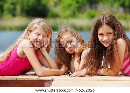 Three girls lie on wooden river bridge - stock photo