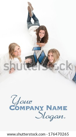 Three girls lying on the floor using each a laptop (aerial view)  - stock photo