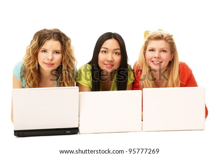 Three girls lying on the floor with a laptop. isolated on white background - stock photo