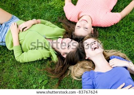 Three girls lying on the grass - stock photo
