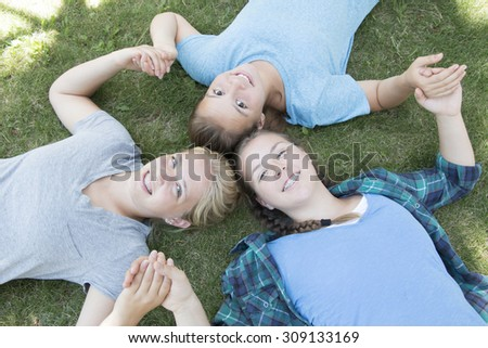 Three Girls Lying on The Green Grass - stock photo