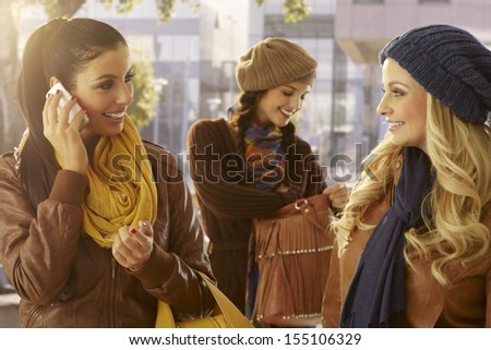 Three girls outdoors, talking on mobile, chatting. Friendship. - stock photo