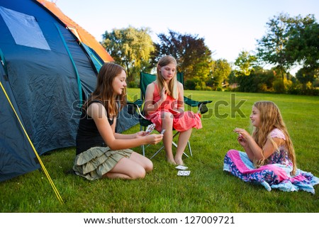 three girls playing card beside their camping tent - stock photo