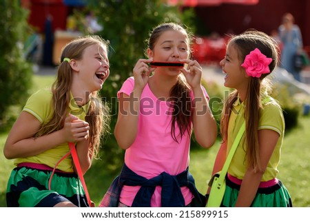 Three girls playing music in the park. The photo shows a cheerful smile on the face of resting human. Close-up. - stock photo