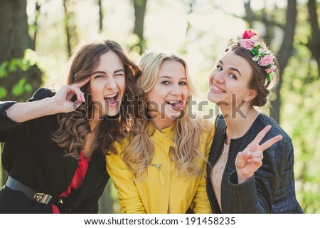 three girls posing for the picture in the park