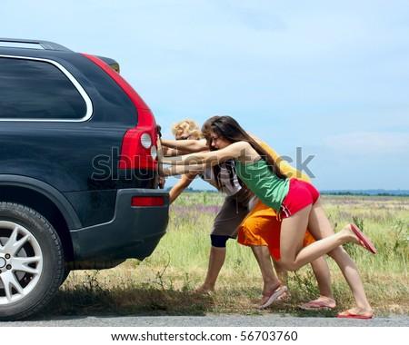 three girls push the broken car - stock photo