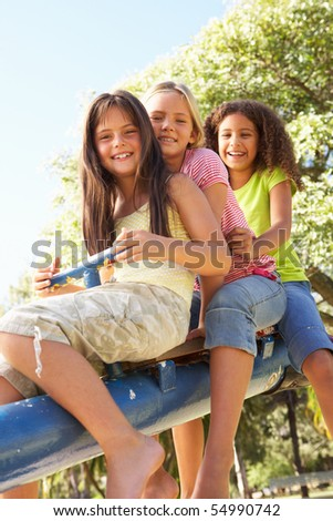 Three Girls Riding On See Saw In Playground - stock photo