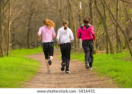 Three girls running through the park - stock photo