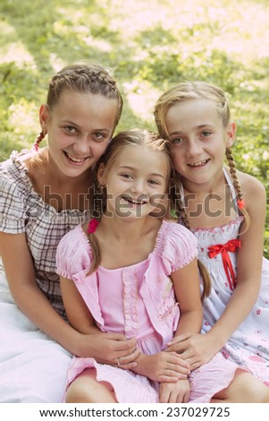 Three girls sit on the grass and smile - stock photo