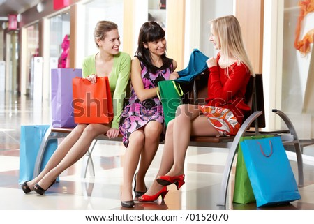 Three girls sitting in shopping mall and showing new clothing - stock photo