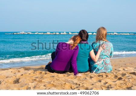 Three girls sitting on a beach - stock photo