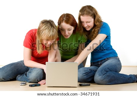 Three girls sitting on the floor with a laptop.  Isolated against a white background. - stock photo