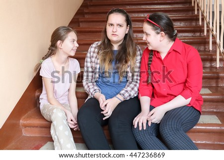 Three girls sitting together on stairs at school, look toward, focus on central girl
