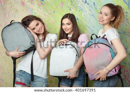 three girls smiling and holding backpacks in studio - stock photo