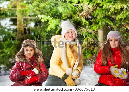 Three girls snowball fighting in the winter forest - stock photo
