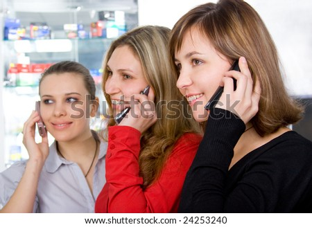Three girls talking by mobile phones at office