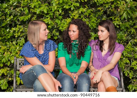 Three Girls Talking Seated on a Bench - stock photo
