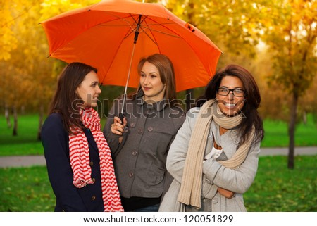 Three girls under one umbrella in the park - stock photo