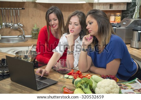 Three girls using computer and cooking in the kitchen. They are leaning on the kitchen counter and searching for a recipe online on laptop.