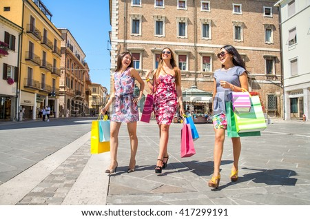 Three girls walking in the city centre while shopping - Best friends hanging out and buying some gifts - stock photo