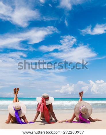 Three girls  wearing a bikini and sun hat sitting on a deserted tropical beach in Bali - stock photo