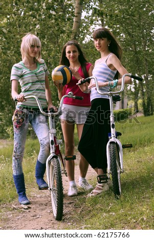 Three girls with bicycle and ball cost(stand) in park