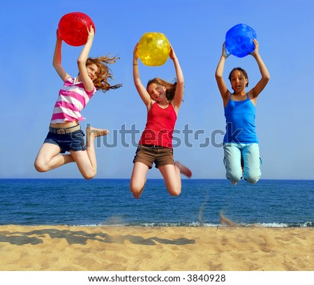 Three girls with colorful beach balls jumping on a seashore - stock photo