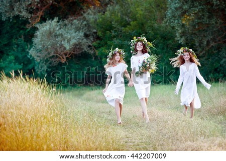 Three girls with wreaths of flowers in their hands. Midsummer. Earth Day - stock photo