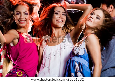 Three glamorous girls having fun at disco in night club