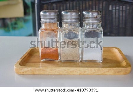 three glass bottoms of cayenne pepper Salt on wood tray
