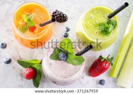 three glass fresh juice smoothie fruit vegetable decorated marble table from above  - stock photo