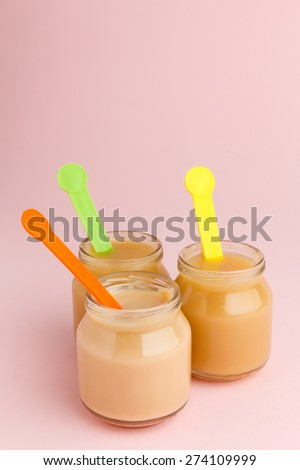 Three glass jars of baby puree with colorful spoons on pink background with copy space - stock photo