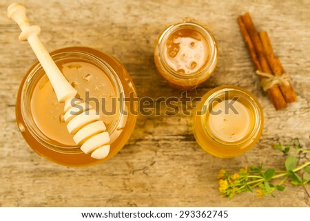 three glass jars of fresh honey with drizzler, cinnamon, flowers on wooden background, top view - stock photo
