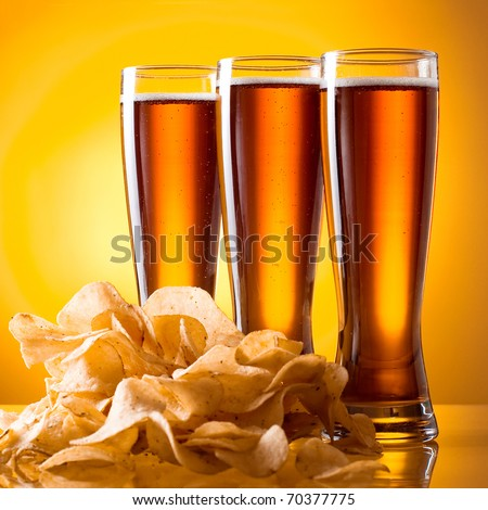 Three glass of beer and potato chips on a yellow background - stock photo