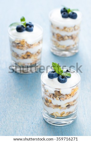 Three glass of dessert with yogurt, cereals and blueberry. - stock photo