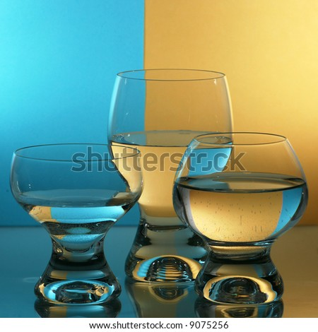 Three glass with blue yellow background. - stock photo