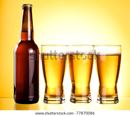 Three glasses and Bottle of fresh light beer on yellow background - stock photo