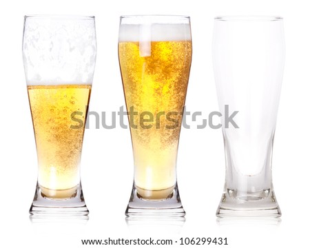 Three glasses of beer with one full, one half gone, and one empty isolated on a white background. - stock photo