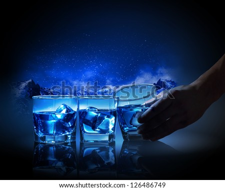 Three glasses of blue liquid with ice against mountain background - stock photo