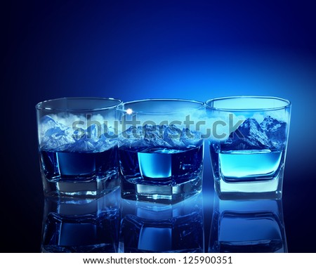 Three glasses of blue liquid with mountain illustration in - stock photo