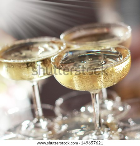 Three glasses of champagne with lights in the background. - stock photo