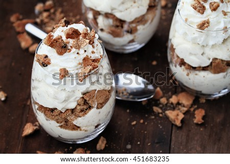 Three glasses of crumbled chocolate chip cookies and cheesecake parfaits against a rustic background. Extreme shallow depth of field with selective focus on dessert in front. - stock photo