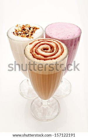 three glasses of milkshakes, caramelshakes and berryshakes cocktails on a white background - stock photo