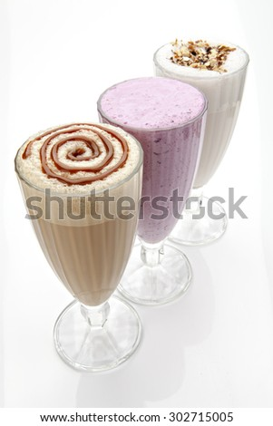 three glasses of milkshakeswith nuts and caramel topping - stock photo