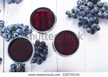 three glasses of red wine and blue grapes on white wooden table background - stock photo