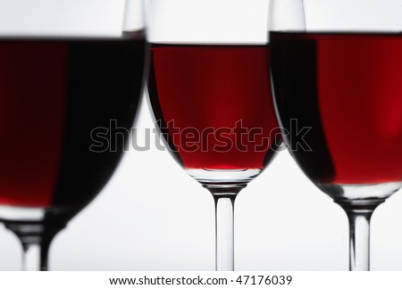 Three glasses of red wine. Focus is on the middle glass.