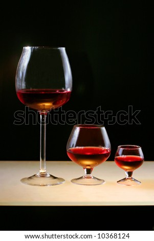 Three glasses of red wine or cognac on  	 lighting bar and on black background.