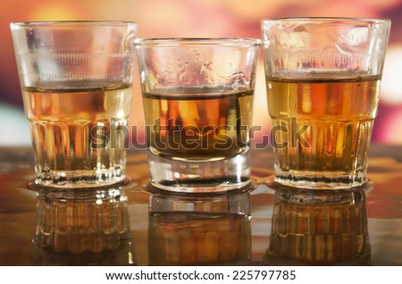three glasses of rum whiskey alcohol on wooden table over defocused lights background - stock photo